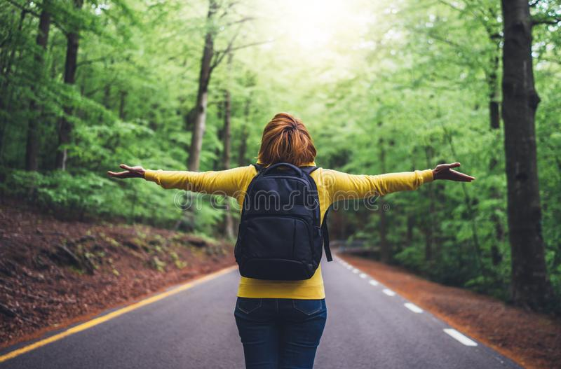 Tourist traveler with backpack standing with raised hands, girl hiker view from back looking into road at forest with arms outstre royalty free stock image