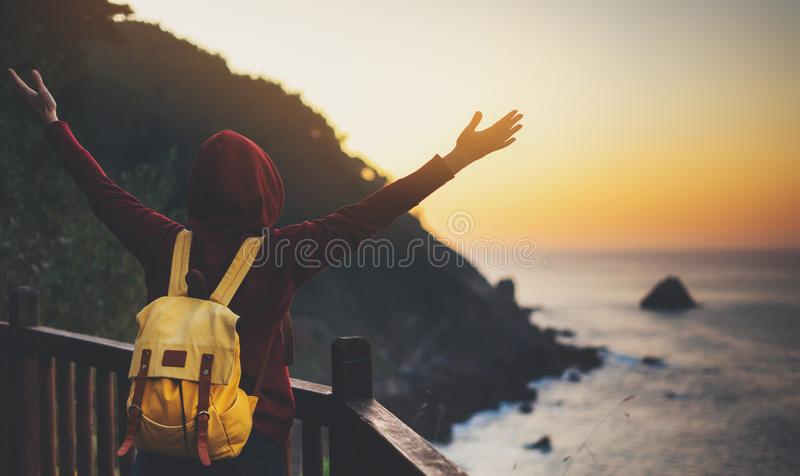 Tourist traveler with backpack standing with raised hands, hiker looking on sunset to valley in trip, hipster young girl enjoying stock photos