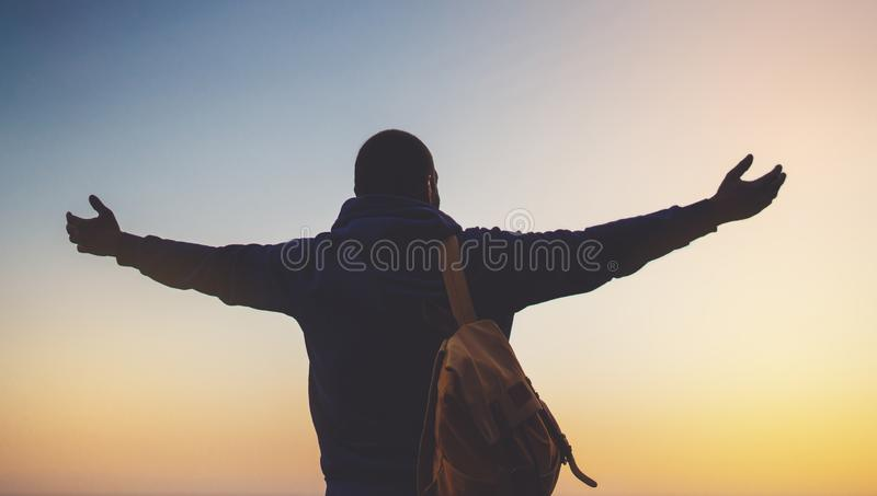 Tourist traveler with backpack standing with raised hands, hiker looking on sunset to valley in trip, hipster young man enjoying stock image