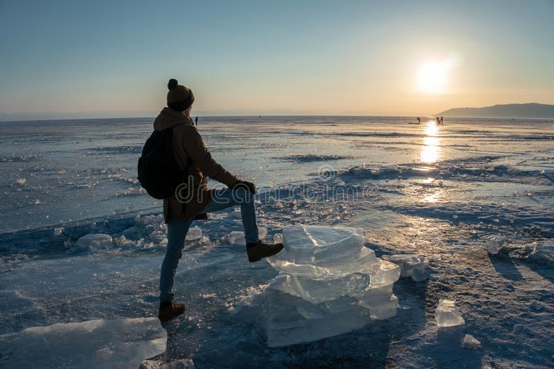 Tourist traveler with a backpack watching the sunset on the snowy ice of lake Baikal. Concept of freedom and travel stock photo