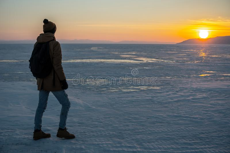 Tourist traveler with a backpack watching the sunset on the snowy ice of lake Baikal. Concept of freedom and travel royalty free stock image