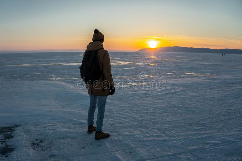 Tourist traveler with a backpack watching the sunset on the snowy ice of lake Baikal. Concept of freedom and travel royalty free stock photo