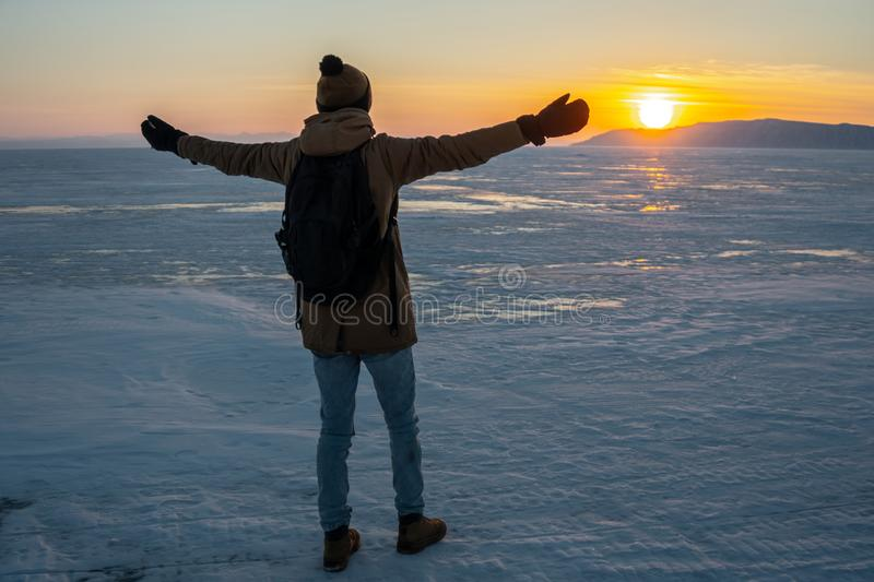 Tourist traveler with a backpack watching the sunset on the snowy ice of lake Baikal. Concept of freedom and travel stock photography