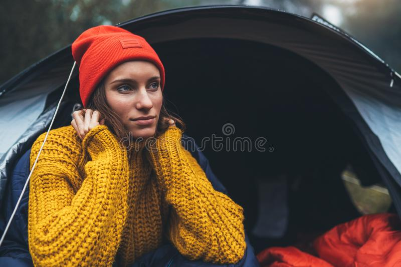 Tourist traveler ralaxing in camp tent in froggy mist forest, portrait lonely hiker woman enjoy nature trip, green trekking royalty free stock photo
