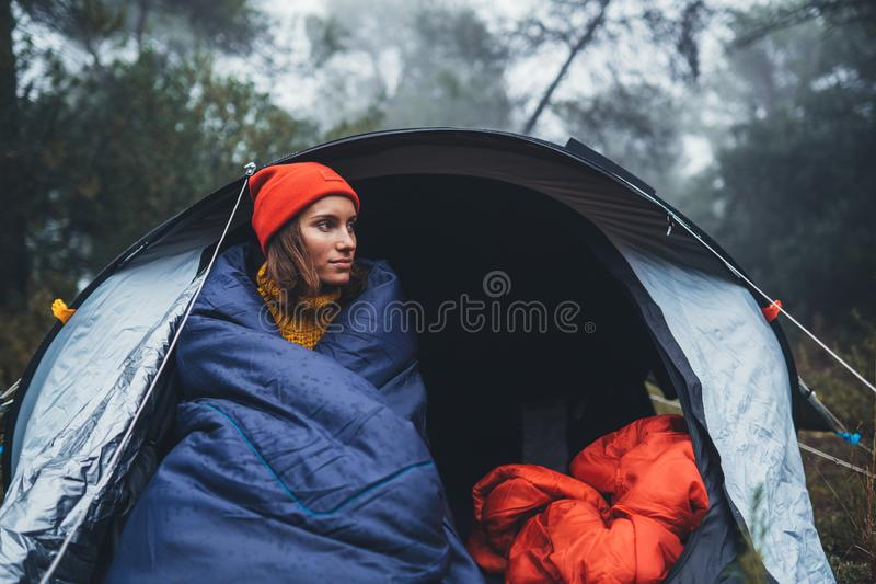 Tourist traveler ralaxing in camp tent in froggy rain forest, hiker woman enjoy mist nature trip, green trekking tourism, rest vac royalty free stock image