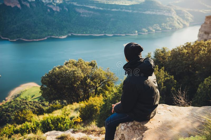 Tourist traveler sits on top mountain and enjoys river, hiker relax looking on blue sky clouds, background nature panoramic landsc royalty free stock image