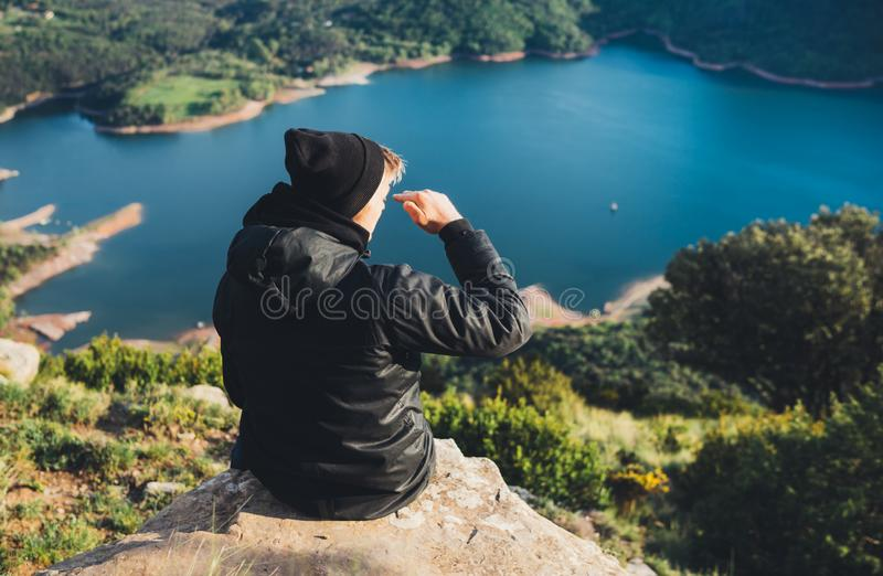 Tourist traveler on top mountain and enjoys river, hiker relax looking on blue sky clouds, background nature panoramic landscape royalty free stock photo