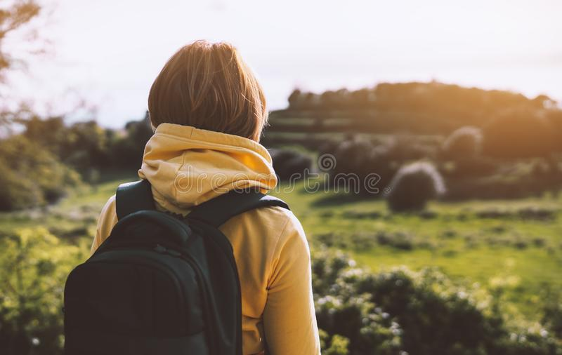 Tourist traveler with yellow backpack standing on green top on mountain, hiker view from back looking on hills and mountain river royalty free stock image