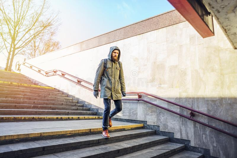 Tourist in urban environment. Tourist man in a hood goes down into the underpass in an urban environment. Tourist in winter city concept royalty free stock photos