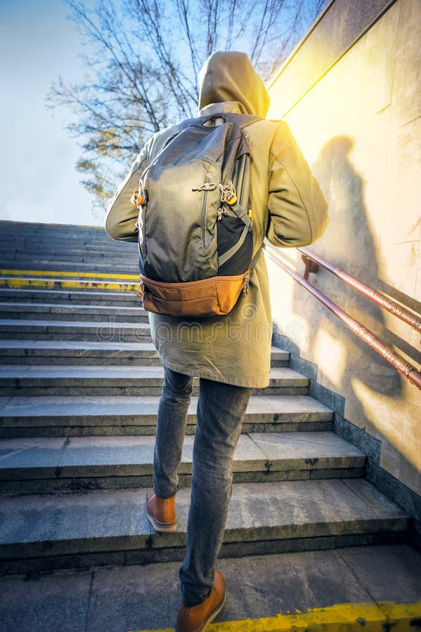 Tourist in urban environment. Tourist man in a hood with a large backpack climbs the stairs at dawn in an urban environment. Tourist in winter city concept stock photo