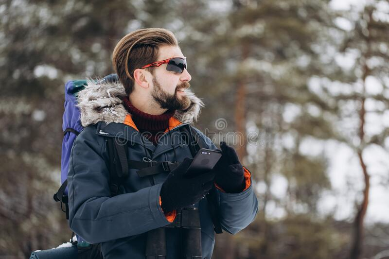 Tourist Using GPS to Route Through Winter Forest. Bearded tourist using GPS on his smartphone to route through winter snow-clad forest royalty free stock photos