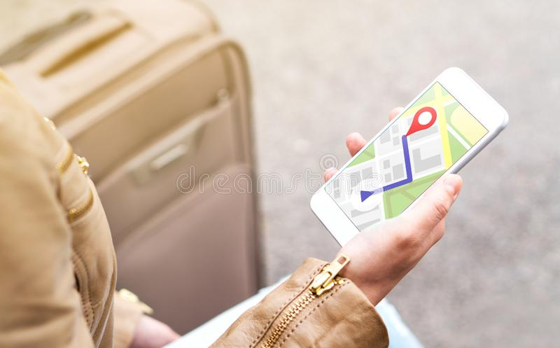 Tourist using map in phone app to navigate and find location. Tourist using map in phone app to navigate and find location of hotel in city. Woman with stock photos