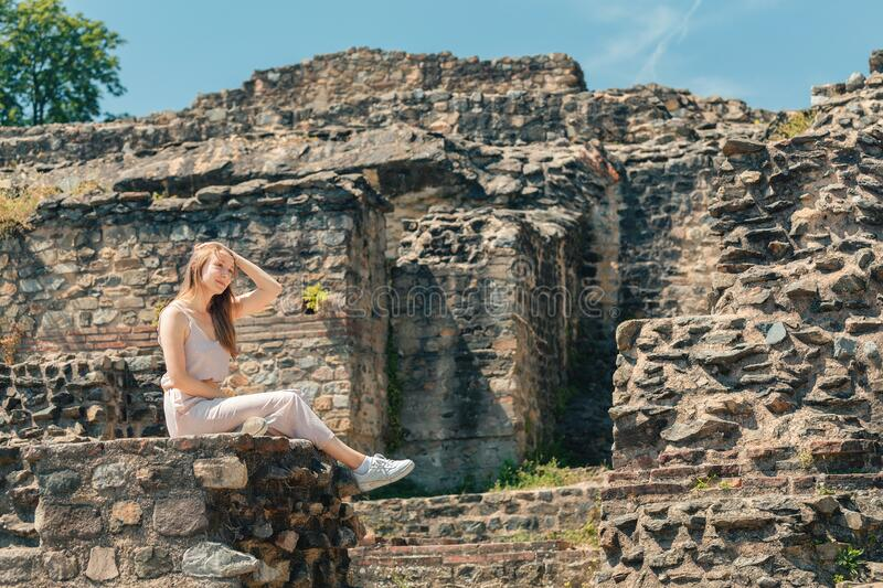 Tourist walking in ancient roman or greek ruines of antique amphitheater. Girl tourist walking in ancient roman or greek ruines of antique amphitheater royalty free stock images