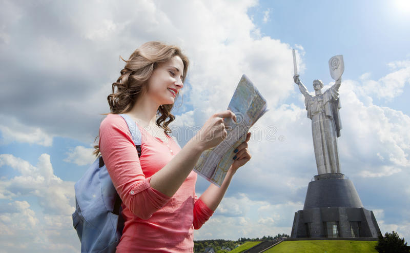 Tourist walking in Kiev the capital of Ukraine. Young tourist pink blouse and blue backpack is examining map of city Kiev capital of Ukraine .Park Slavy royalty free stock photos