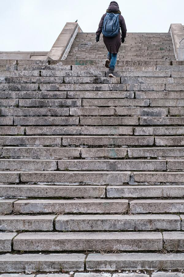 Tourist in warm clothes and with an urban backpack walks up the old stone steps of a high staircase on a winter day. Tourist in warm clothes and with an urban royalty free stock images