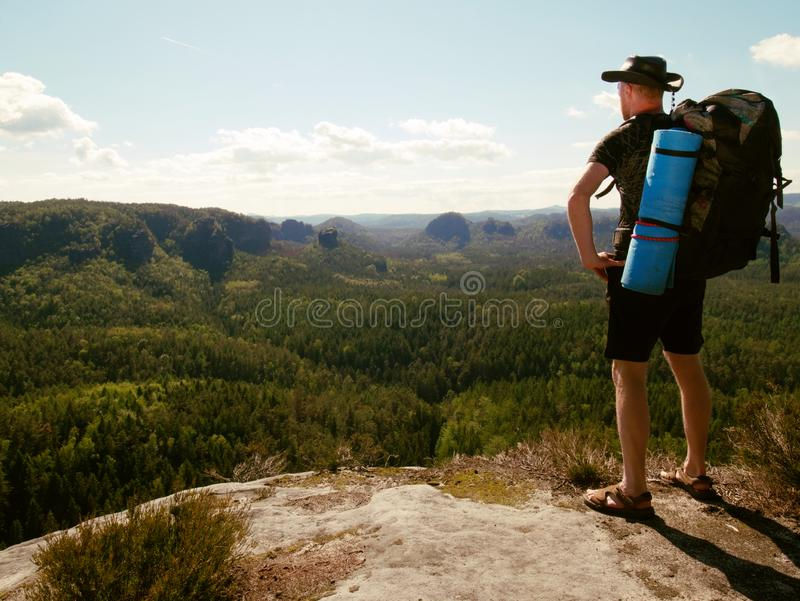 Tourist watch land from mountain top. Man wear backpack. Tourist watch land from mountain top. Man wear big backpack against sun light, walk, view, valley royalty free stock photo