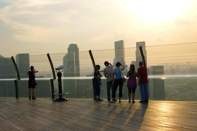 Tourist watching sunset against Singapore skyline. Tourists on rooftop looking at Singapore skyline at sunrise or sunset royalty free stock photos