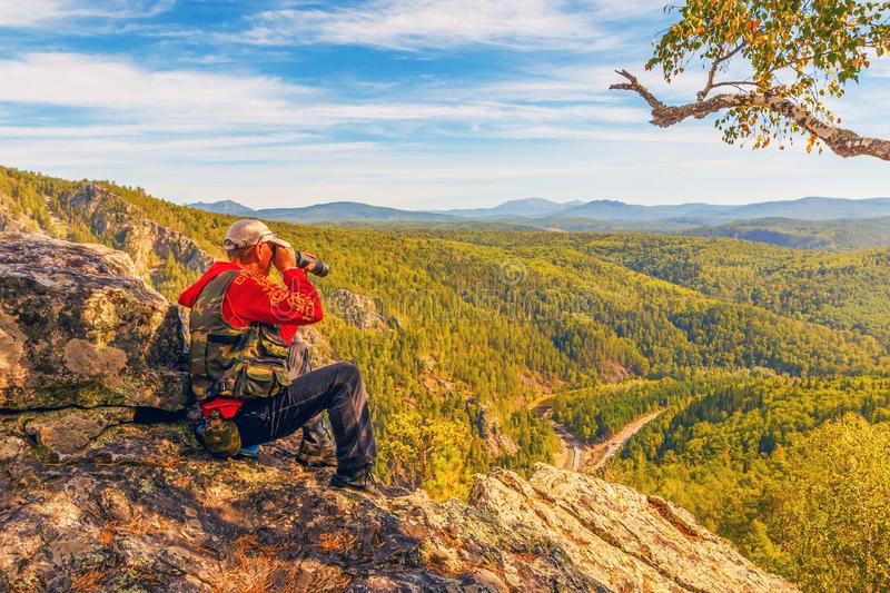 A tourist who is on a rock looks out into the distance to the Ural Mountains. A sunny day stock photography