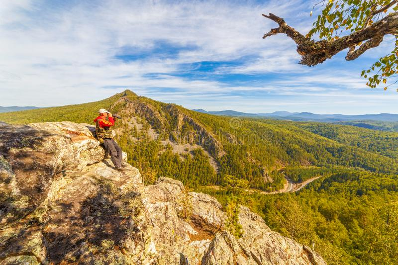A tourist who is on a rock looks out into the distance to the Ural Mountains,. A sunny day stock photos