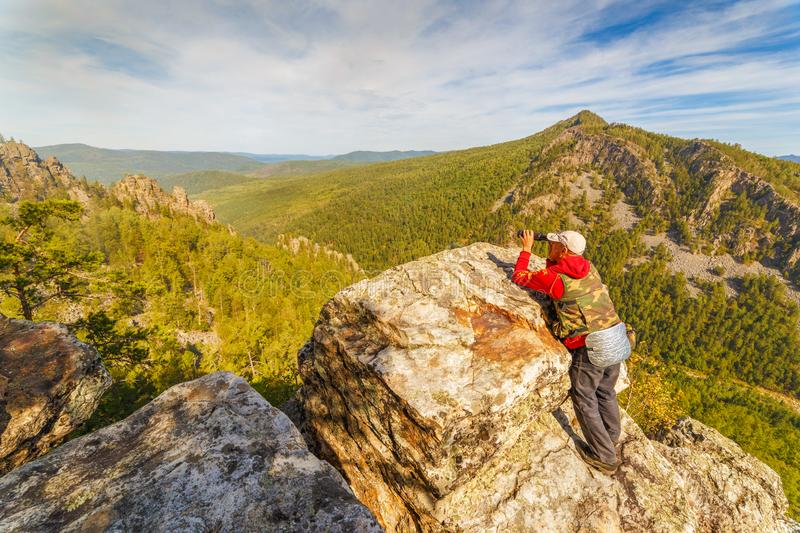 A tourist who is on a rock looks out into the distance to the Ural Mountains,. A sunny day stock images