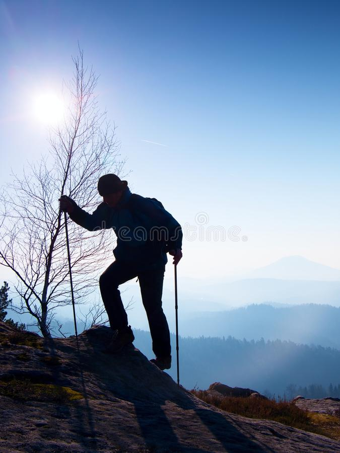 Tourist in windcheater is climbing with poles in hands to rocky view point above deep misty valley. Nice spring daybreak in rocks stock images