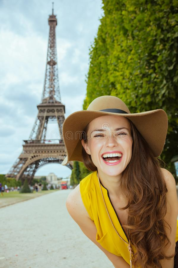 Tourist woman against clear view of Eiffel Tower. Portrait of happy modern tourist woman in yellow blouse and hat against clear view of the Eiffel Tower in Paris royalty free stock photo