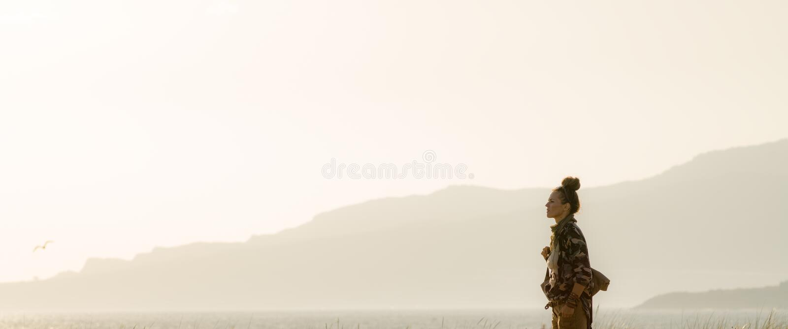 Tourist woman against mountain and ocean landscape at sunset. Fit tourist woman in hiking clothes against mountain and ocean landscape at sunset stock photo