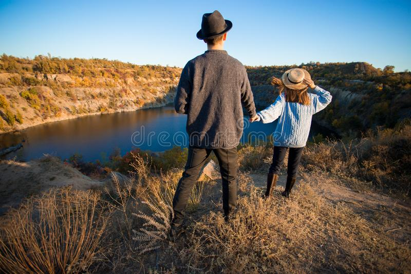 Tourist woman in black hat holding man by hand and go to lake in autumn mountains. royalty free stock photo