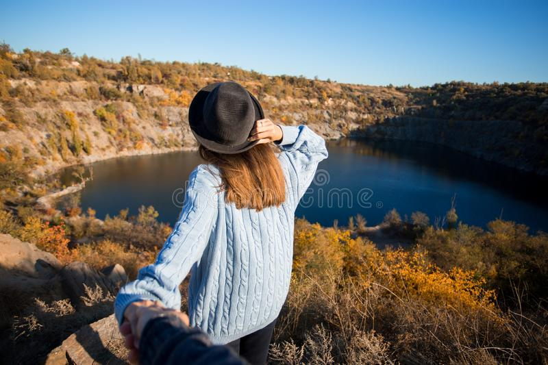 Tourist woman in black hat holding man by hand and go to lake in autumn mountains. royalty free stock images