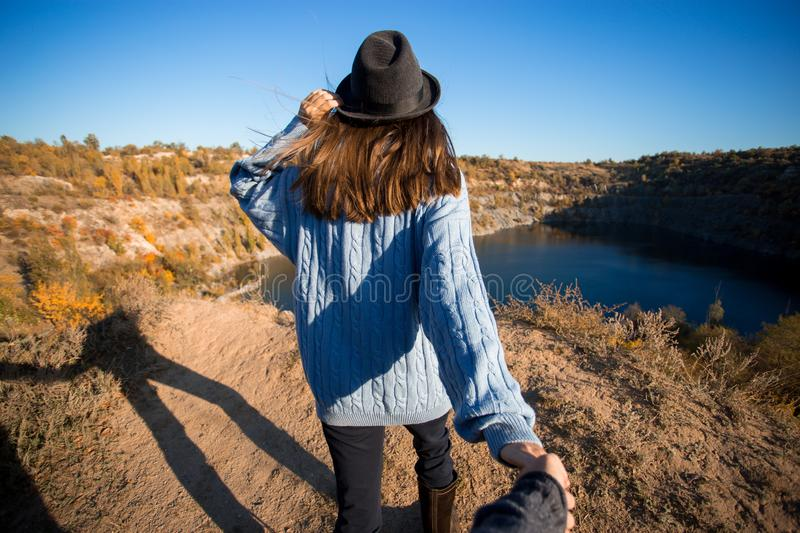 Tourist woman in black hat holding man by hand and go to lake in autumn mountains. stock photos
