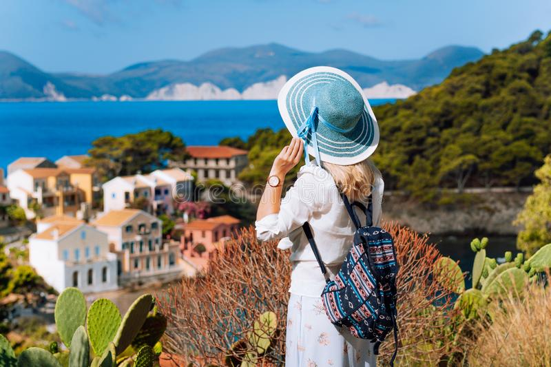 Tourist woman with blue sunhat, white clothes and travel backpack admire view of colorful tranquil village Assos on royalty free stock photo