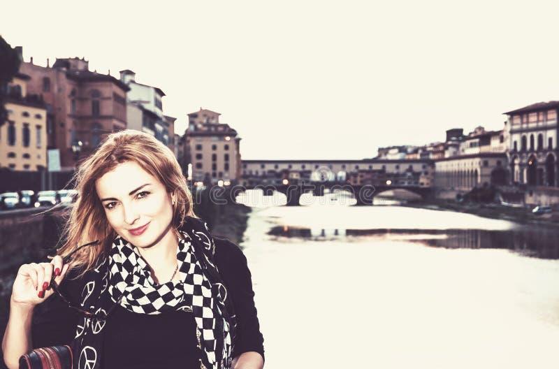 Tourist woman with bridge Ponte Vecchio, Florence, vintage filter. Beautiful young tourist woman posing in front of amazing bridge Ponte Vecchio, Florence stock photography