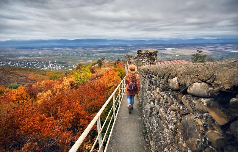 Traveler at city wall in Signagi. Tourist woman in brown hat and backpack walking on the ancient city wall with view to Alazani valley at autumn time in Signagi stock photography