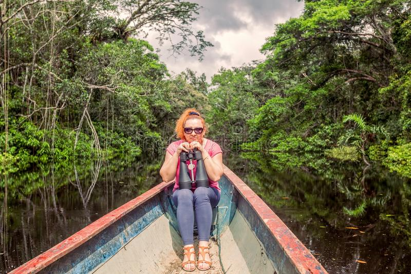 Tourist Woman In A Canoe With High Power Binocular. Happy Tourist Woman In A Canoe With High Power Binocular In Amazonian Jungle, National Park Cuyabeno, South stock images