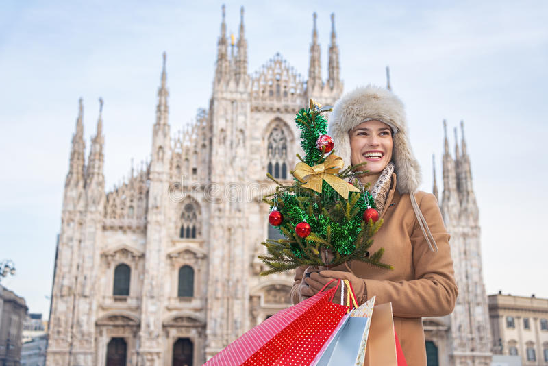 Tourist woman with Christmas tree and shopping bags in Milan royalty free stock photos