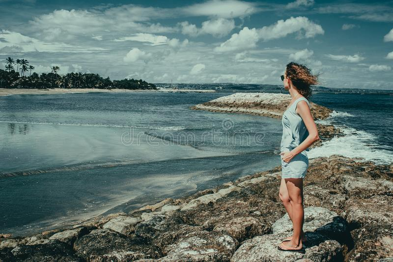 Tourist woman enjoy vacation on Kuta beach. Bali traveller. Explore beautiful Indonesia landscape. People travel. Tourism concept. Bright windy day. Tropical stock images