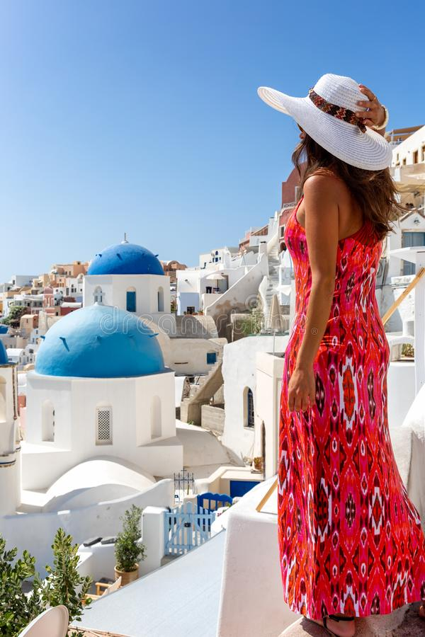 Tourist woman enjoys the view to the blue domed churches of Oia on the island of Santorini, Greece stock photo