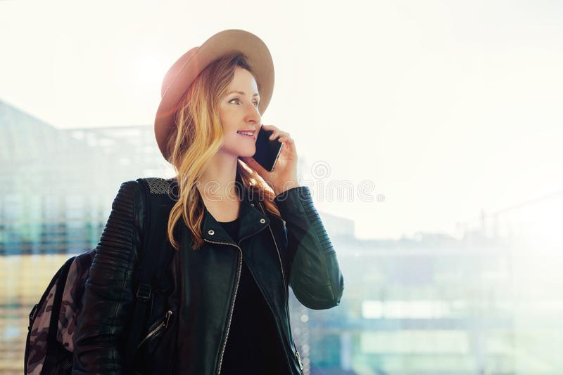 Tourist woman in hat with backpack is standing at airport and talking on cell phone. Girl stands, uses digital gadget. Young tourist woman in hat and with stock photos