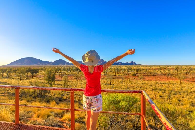 Tourist woman in Australian Outback. Tourist woman in hat enjoying from platform dune viewing area enjoys Mount Olga in Uluru-Kata Tjuta National Park at sunset stock image
