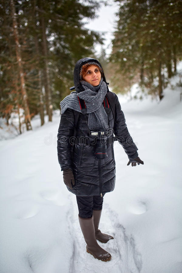 Tourist woman hiking with camera. Tourist woman with camera hiking on a snowy trail in the mountains royalty free stock photos