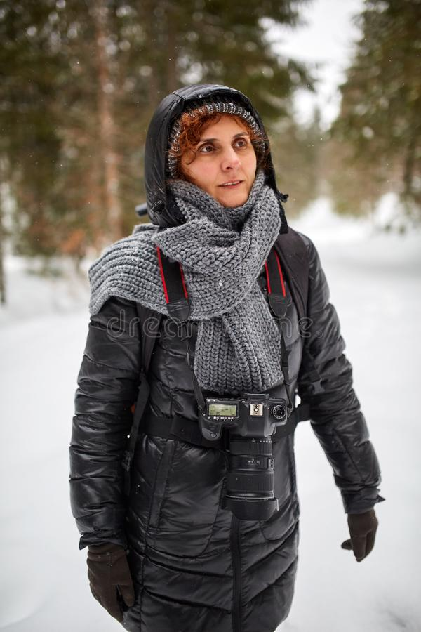 Tourist woman hiking with camera. Tourist woman with camera hiking on a snowy trail in the mountains stock photography