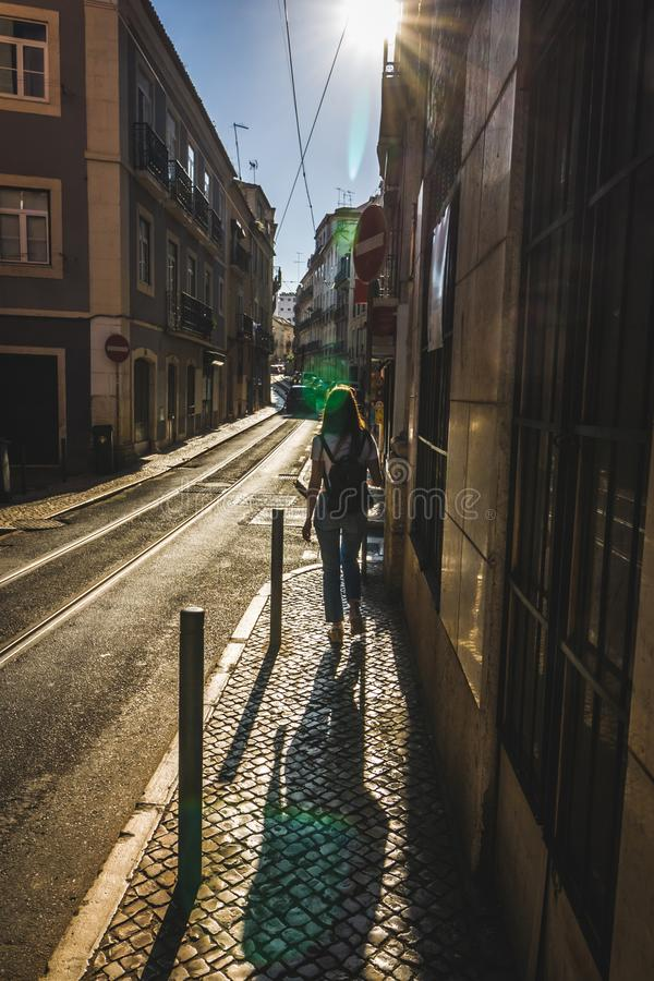 Tourist woman in jeans, a white t-shirt and a black backpack walks the streets of Lisbon. Cityscape narrow streets of the old town stock photography
