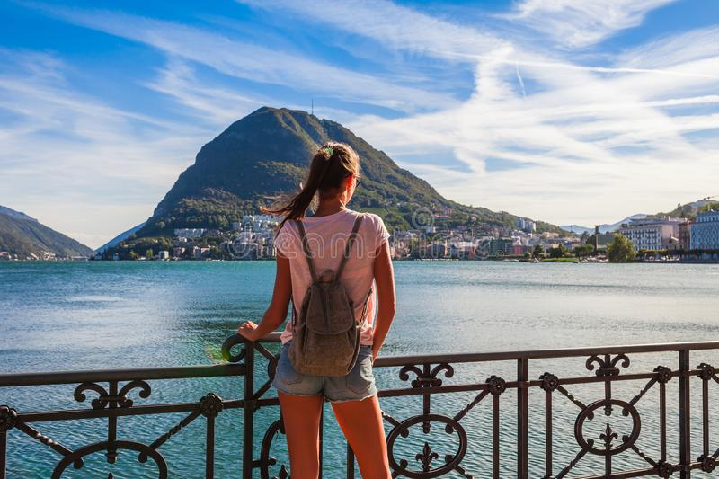Tourist woman of the lake Lugano, mountains and city Lugano, Ticino canton, Switzerland. Traveler in scenic beautiful Swiss town. With luxury villas. Famous stock photo