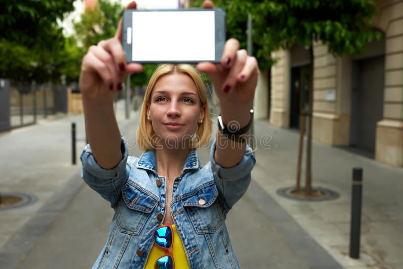 Tourist woman making self portrait with mobile phone digital camera during her vacation holidays in summer royalty free stock photography