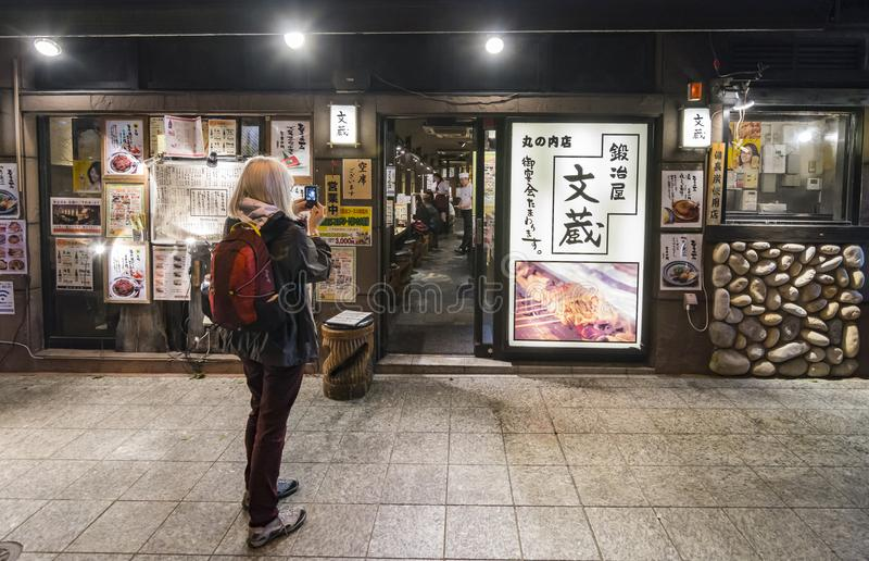 Tourist woman photographing restaurant Chiyoda Tokyo stock photo