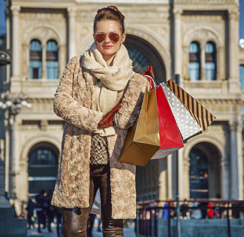 Tourist woman at Piazza del Duomo in Milan, Italy standing. Rediscovering things everybody love in Milan. elegant tourist woman with shopping bags at Piazza del stock photography