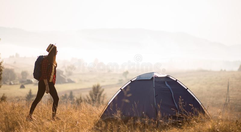Tourist woman relaxing alone with large backpack enjoying autumn sunrise view on top of mountains. royalty free stock images