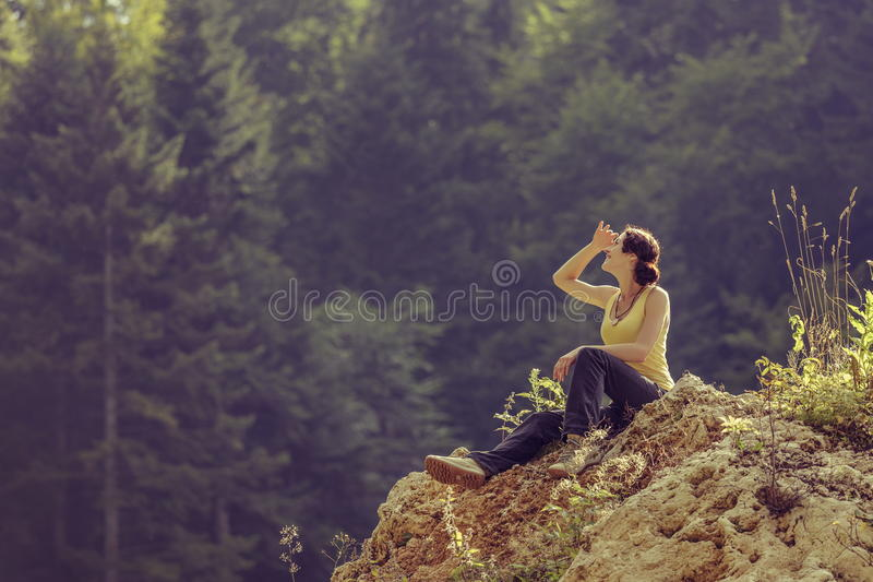 Tourist woman resting on rock stock photography