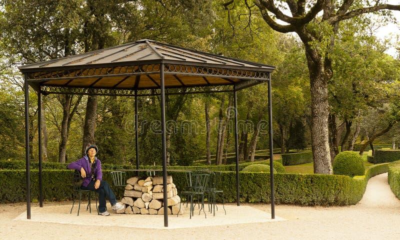 Woman resting pavillion Le Jardin Marqueyssac France. Tourist woman resting under a pavillion at Le Jardin Marqueyssac gardens in Dordogne France royalty free stock photos