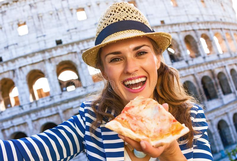 Tourist woman in Rome, Italy with pizza slice taking selfie. Roman Holiday. happy young tourist woman in Rome, Italy with pizza slice taking selfie stock photo